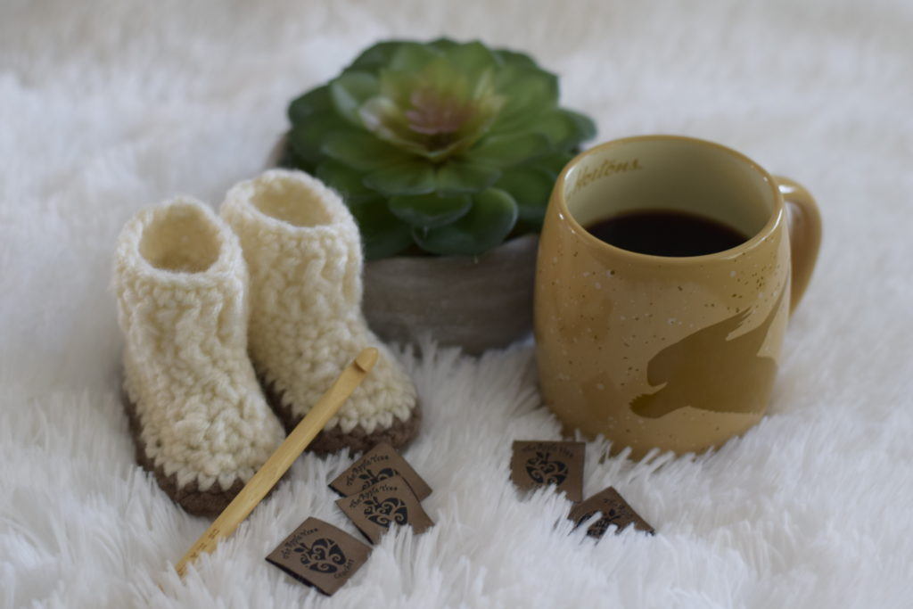 crochet baby slipper boots and coffee on white fir blanket 2
